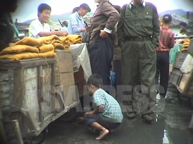 암시장에서 어린이가 땅바닥에 떨어진 국수 조각을 줍고있다. '고난의 행군기' 1998년 10월 강원도 원산시에서 촬영 안철(아시아프레스)