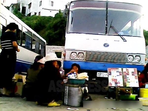 버스 승객을 대상으로 담배(오른쪽), 음식, 음료를 파는 인근의 여성들. 중국 지방도시에서 볼 수 있는 광경과 같다. 2013년 9월 평안남도 평성시에서 촬영 '민들레'(아시아프레스)