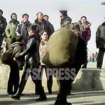 A woman, ostensibly a peddler, humping a huge khaki backpack. It is mostly women who engage in such informal business in North Korea. (Sinuiju Station, North Pyongan Province. November. 2012.) ASIAPRESS
