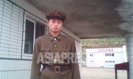 """A member of the """"Worker-Peasant Red Guards"""" stands in front of the entrance to a state run enterprise. (Taken by Kim Dong-cheol, South Pyongan Province, October 2010.) . ASIAPRESS"""