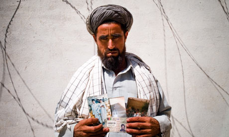 Fazel Muhamad Fazel Muhamad, 48, holding pictures of family members who were killed in the attack. Photograph: Ghaith Abdul-Ahad