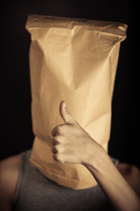 Preteen boy covering his face with a paper bag and showing thumbs up