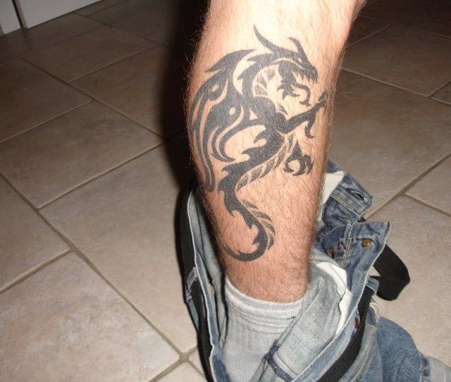 Black Ink Tribal Dragon Tattoo On Right Leg Calf