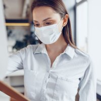 Young medical assistant in facemask with clipboard