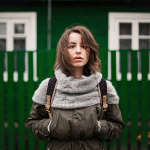 young woman in coat with green fence