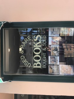 used book store front window promoting used and rare books bought and sold