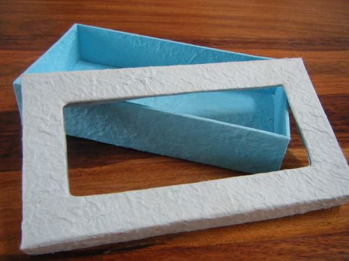 A box ready to be made into a prettier box - blue box base and a white lid with a rectangle gap in the middle