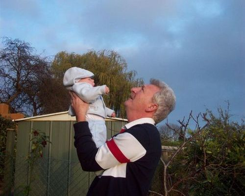Grandad holding baby Grandson up to the sky