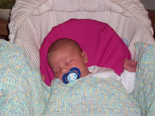 Baby under a homemade crochet blanket
