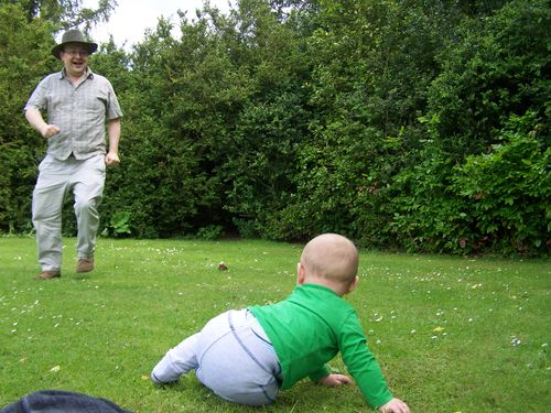 TJ laughing and running towards little man on the grass