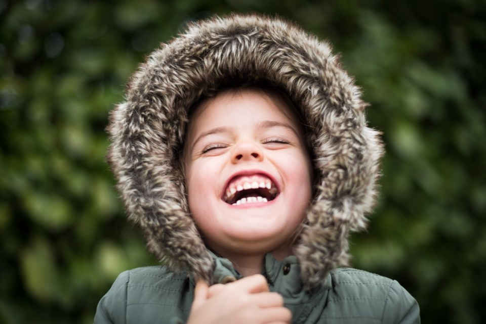 images of a young child wearing a winter coat with a fur hood, laughing with their eyes closes