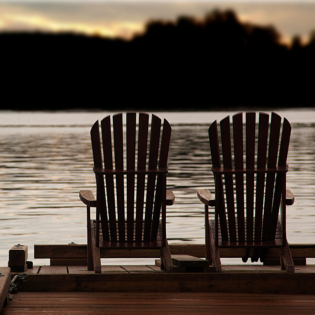 Two Chairs looking out over a lake at sunset