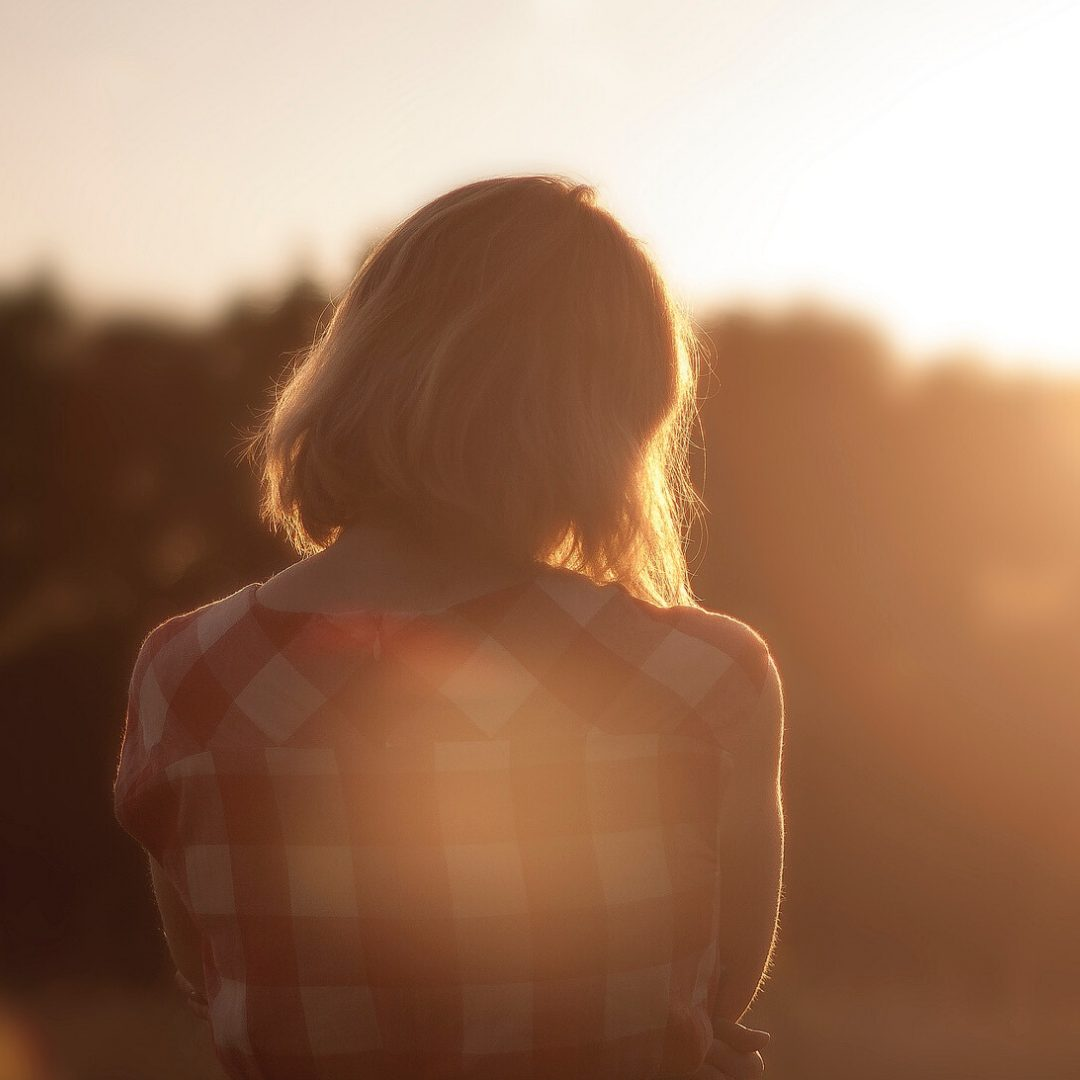 Image of a girl in a checked shirt looking into the sunset