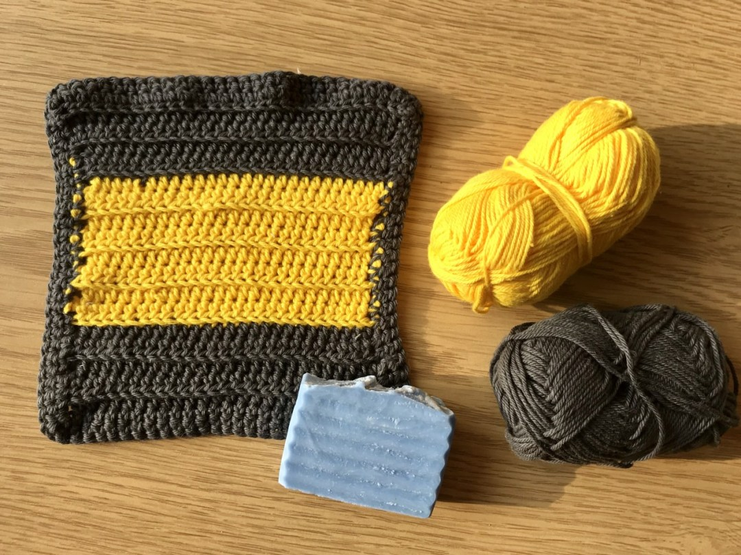 Image of a grey and yellow crochet washcloth, with yarn beside it and a bar of blue handmade soap