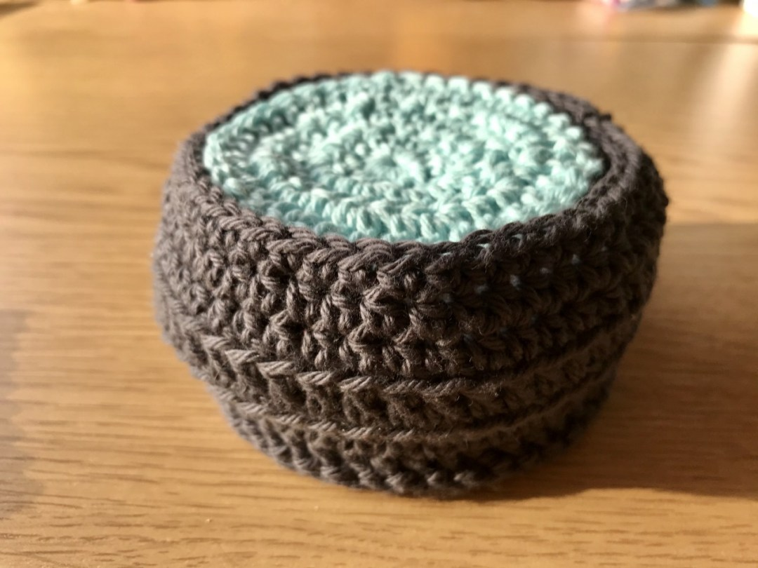 Image of grey crochet basket filled with crochet face pads