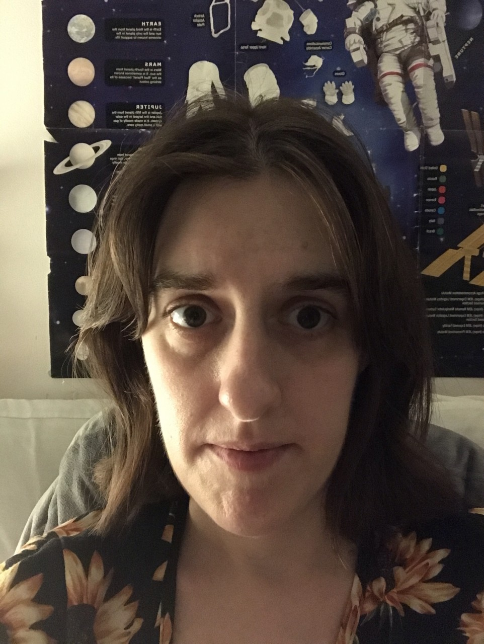 Image of Amanda (a mid-30s woman with dark hair and dark eyes) looking into the camera. She has bags under her eyes and is sitting in front of a Space poster in her son's bedroom.