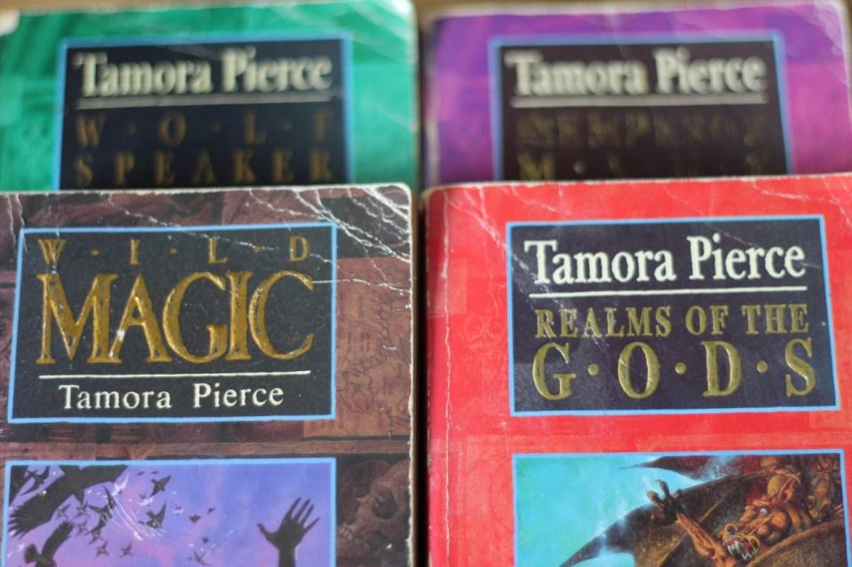 4 Tamora Pierce books, Wild Magic, Wolf Speaker, Emperor Mage, and Realms of the Gods