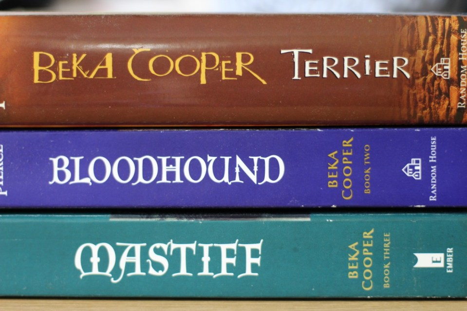 stack of three books by Tamora Pierce, Beka Cooker Terrier, Bloodhound, and Mastiff