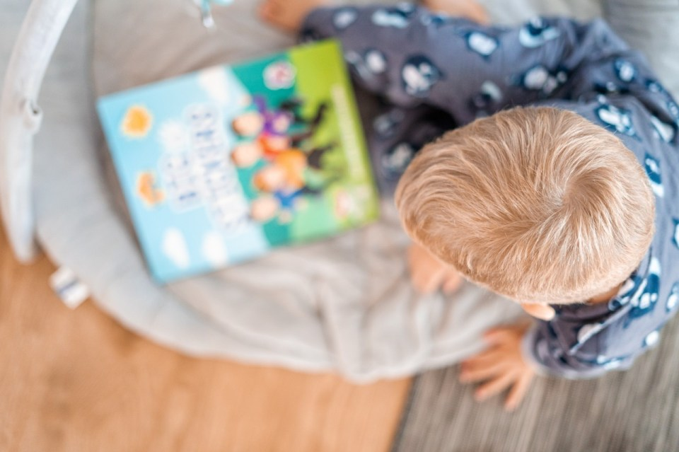 overhead view of a young child sitting on a beanbag reading a book