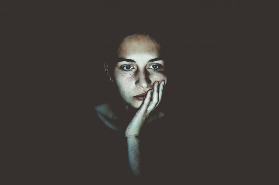 a womane with her hand under her chin looking bored on a dark background