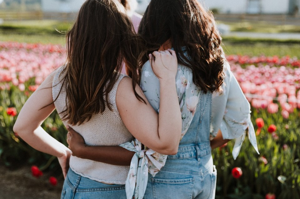Two women standing in front of a garden of flowers, both with their backs to the camera, and with their arms around each other