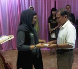 Dewi Hastuty Sjarief menyerahkan Buku 9 Pengakuan kepada Ayahanda Syarifuddin Pasmar