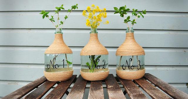 3 garrafões de vinho com corda em volta e flores