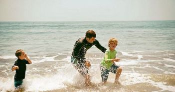 pai e filhos brincando na orla do mar