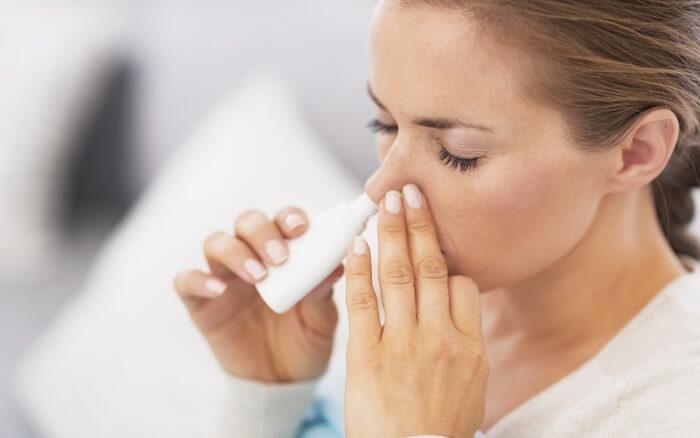 Mulher colocando spray nasal