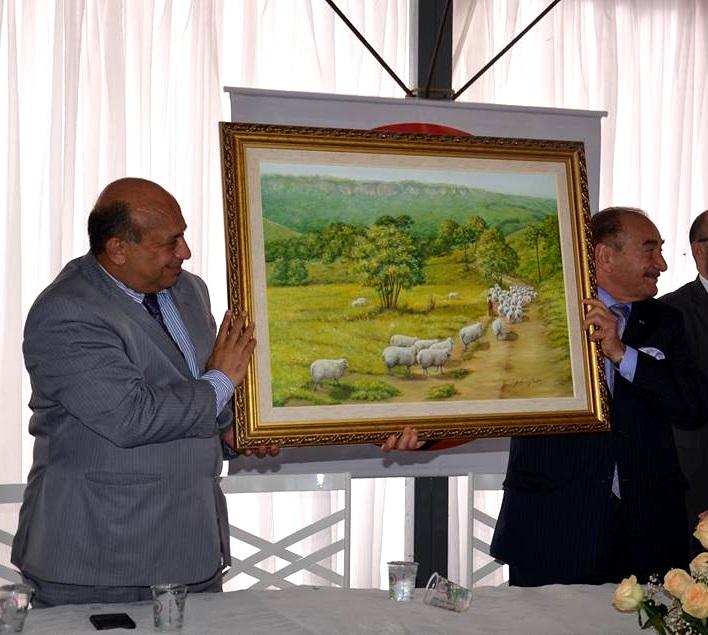 هدية رئيس بلدية جاغوارييفا خوسيه سلوبودا إلى سير نظمي أوجي الذي يحملها مع غسان صعب: لوحة زيتية عن مراعي البلدة الخضراء
