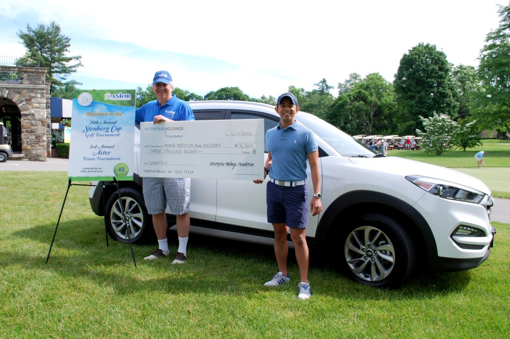 Astor's CEO, Dr. Jim McGuirk, accepting a donation from Jose Jalandoni of Enterprise Fleet Management, sponsor of the Hole in One challenge at our Golf Tournament. Jose is also a member of Astor's Golf Committee.