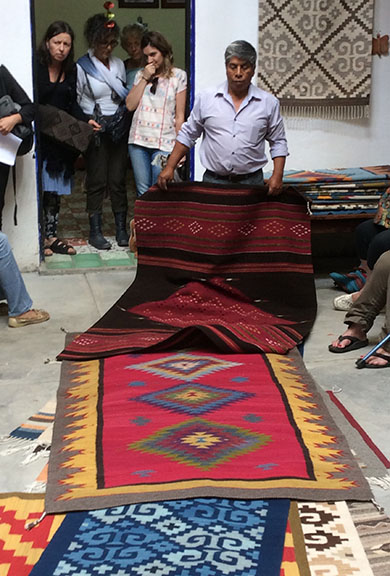 Federico shows us beautiful examples of rugs he and Delores have woven. Color is derived only from natural dyes or the natural wool color. Dolores tends to all the fringes, tucking them in, braiding them, and more.