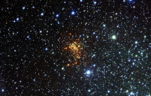 Imagen del cúmulo de estrellas en el que se encuentra Westerlund 1 26. Si te fijas en el centro de la imagen, verás que hay tres estrellas verdes formando un triángulo. Westerlund 1 26 está justo debajo, a la derecha.