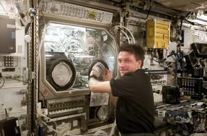 El comandante de la expedición 8, Michael Foale, examina la caja de guantes de microgravedad en la Estación Espacial Internacional. Crédito: NASA/Crew of Expedition 8