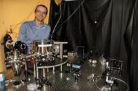 Andre Geraci bij een apparaat dat lijkt op de gravitatiegolf-detector die hij heeft voorgesteld