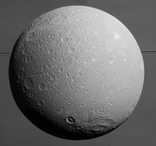 Deze detailrijke foto van Saturnusmaan Dione is op 17 augustus 2015 gemaakt door de ruimtesonde Cassini. Op de achtergrond is het ringenstelsel van Saturnus te zien. (NASA/JPL-Caltech/Space Science Institute)