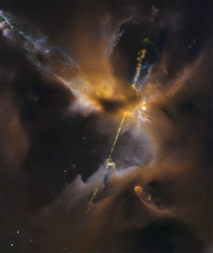 The two lightsabre-like streams crossing the image are jets of energised gas, ejected from the poles of a young star. If the jets collide with the surrounding gas and dust they can clear vast spaces, and create curved shock waves, seen as knotted clumps called Herbig-Haro objects.