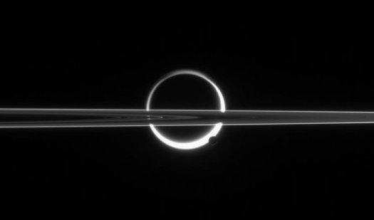 Satürn'ün halkalarının önünde iki uydu: Titan ve Enceladus. Titan'ı çevreleyen beyaz ışığın bulanık olmasının nedeni, uydunun yoğun armosferinden süzülerek geçen ışığın kırılmasıdır.