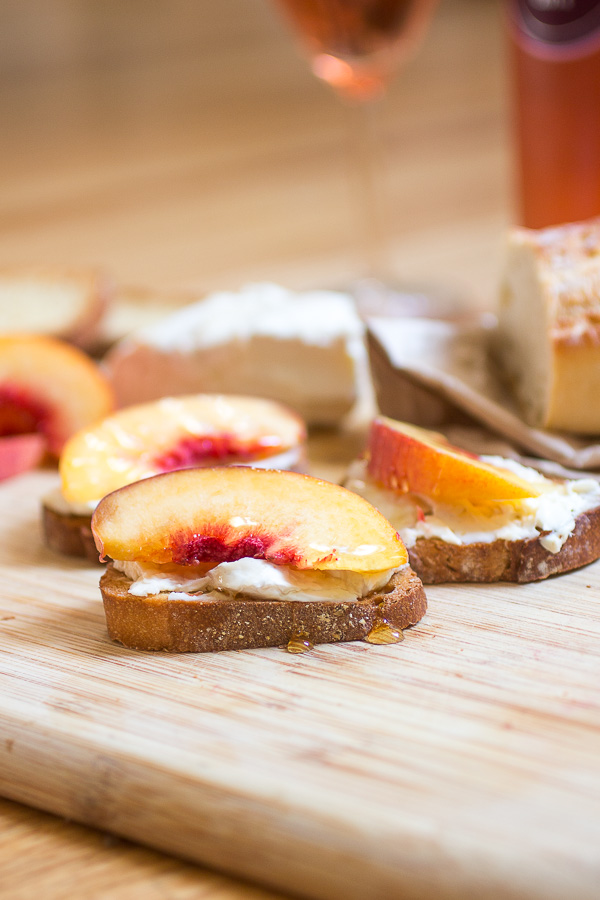 Decadent french cheese crostini with fresh peaches and honey paired with rose