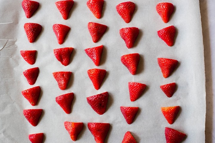 Halved strawberries placed on a lined baking sheet, ready to be frozen to make strawberry frozen yogurt