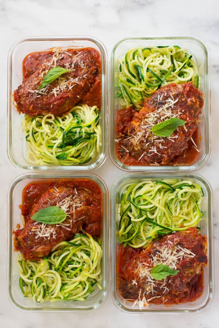 An overhead image of four glass containers each with a serving of Healthy Chicken Parmesan served with zucchini noodles ready to be placed in the refrigerator for meal prep.