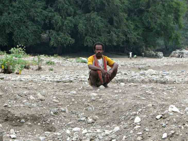 Squatting man at Noelmina Beach, Timor, Indonesia