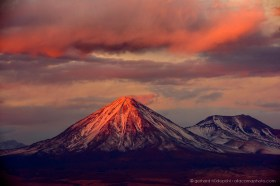 Snow covered volcanoes Licancabur and Juriques illuminated by impressive evening light