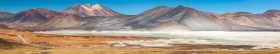 Panorama of colorful Altiplano around Salar de Aguas Calientes in Chile with green lagoon and volcanoes