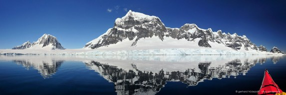 Fief mountain range at Port Lockroy reflecting in the water, perfect day for kayaking in Antarctica