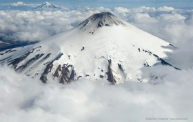 Flying above the clouds, aerial view of volcanoes Villarica and Lanin
