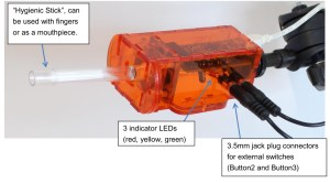 "Labeled photo of Flipmouse: ""Hygienic Stick"", can be used with fingers or as a mouthpiece. 3 indicator LEDs (red, yellow, green) 3.5mm jack plug connectors for external switches (Button2 and Button3)"