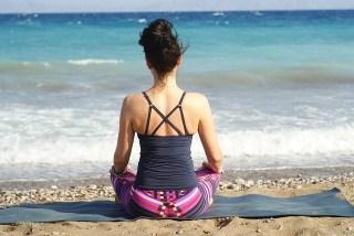 girl sitting on a beach doing yoga