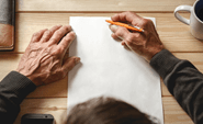 Elderly person writing with pen and paper