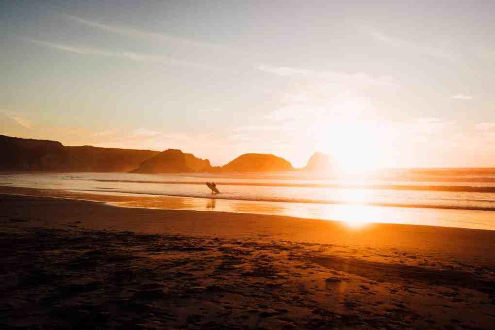 Surfer mit Longboard in der auslaufenden Brandung bei Sonnenuntergang